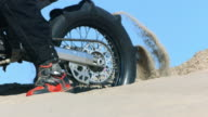 Closeup of motorcycle tire spinning in sand, slow motion video