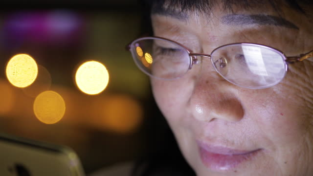 close-up of old woman using mobile phone at home video