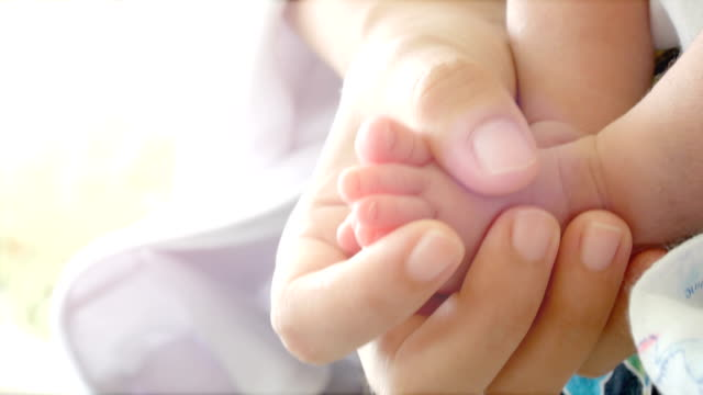 Close-up of parents hands holding feet newborn and baby sleep on her arms. Concept of happy family desire in no noisy home and carefree video