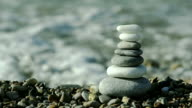 Close-up of pebbles stack, on sea background video