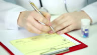 Close-up of physician's hands writing medical prescription, refilling medication video