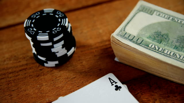 Close-up of playing cards, dollar and casino chips on poker table 4k video