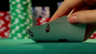 Closeup of poker player's hand checking cards, holding two aces, video