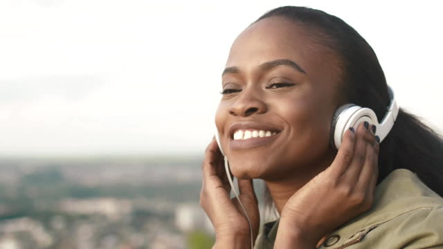 Close-up of pretty young african american woman listening music and relaxing on the blurred city background video
