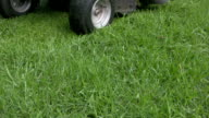 Close-up of Ride-on Lawn Mower with Grass Cuttings Scattering video