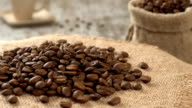 Close-up of roasted coffee beans rotating on burlap. Rustic wooden background. Seamless loopable video