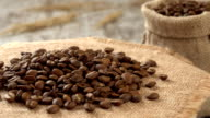 Close-up of roasted coffee beans rotating on burlap. Rustic wooden background. Seamless loopable. Prores FullHD video
