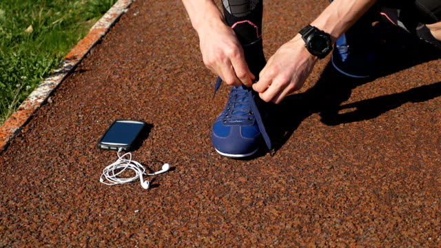 Closeup of runner tying shoelace then picking up smartphone with hands free headphones and starts running on track video
