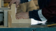 Close-up of running a board of lumber through a wood jointer power tool video