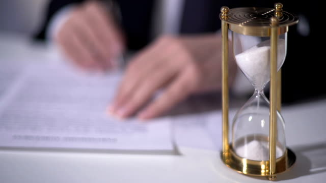 Closeup of sand clock measuring time, businessman signing important contract video