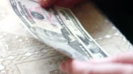 Closeup of senior lady hands with dollar bills, toned color, selective focus, very shallow DOF video