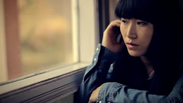 Close-up of serene Asian girl sitting near window. video