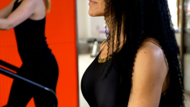 Closeup of slim attractive woman with smart watch doing weight loss exercises on modern gym equipment video