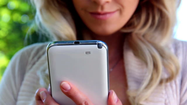 Closeup of smiling blond girl writing message touch phone sms video