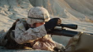 Close-up of Sniper Lies Down on the Hill, Aims through the Rifle Scope and Shoot in Desert Environment video
