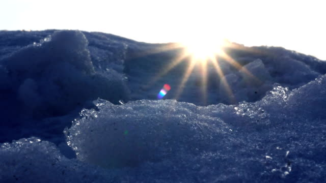 close-up of snowing cold mountains with bright warm rays on slnechnyi background video