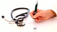 Close-up of stethoscope and doctor's hand writing a medical prescription video