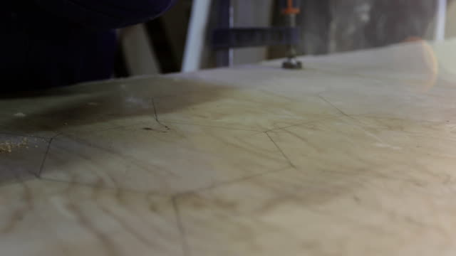 4K Close-up of the carpenter's hand holding a screwdriver and making holes in the chipboard. video