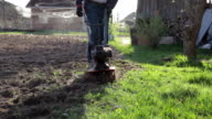 Closeup of the garden cultivator digging over soil in the vegetable garden video