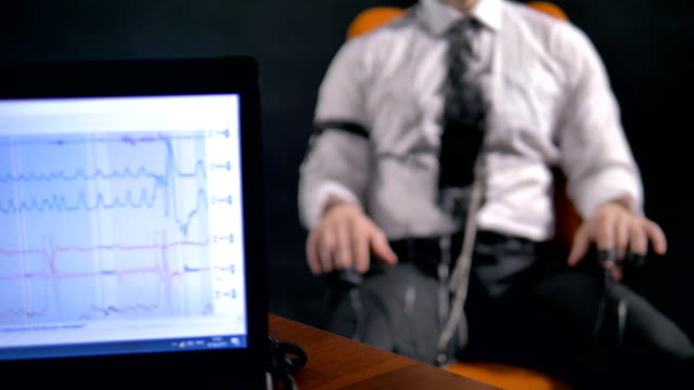 Close-up of the laptop and the man connected to the lie detector circuit. video