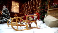 Close-up of the sled on the background of a wooden house with twinkling garlands video