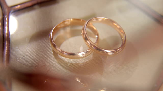 Close-up of two wedding rings on beige background. video