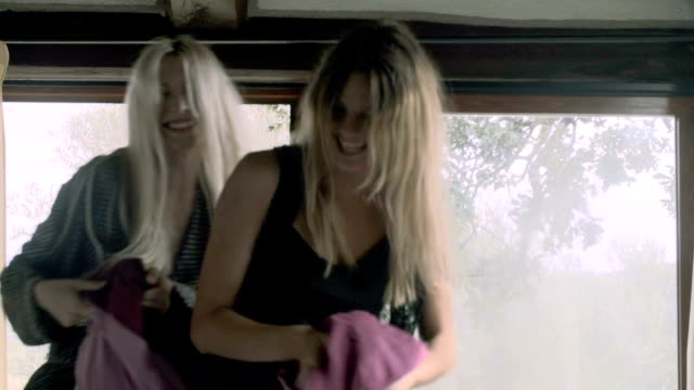 Close-up of two young women, friends or homosexual lesbian couple, do a pillow fight on bed in the morning - slow-motion HD video footage video