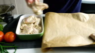 Closeup of woman cook hands put into platter chiken wings in kitchen at home video