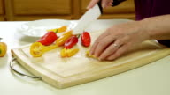 closeup of woman cutting peppers video