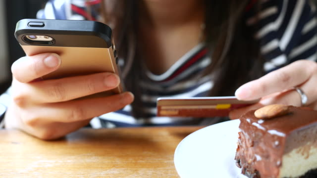 Close-up of woman shopping online on Mobile phone with chocolate cake, 4K(UHD) video
