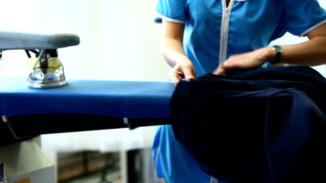 Close-up of woman steaming jacket in laundry video