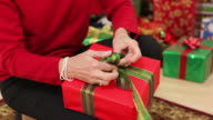 Closeup of woman tying bow on Christmas gift video
