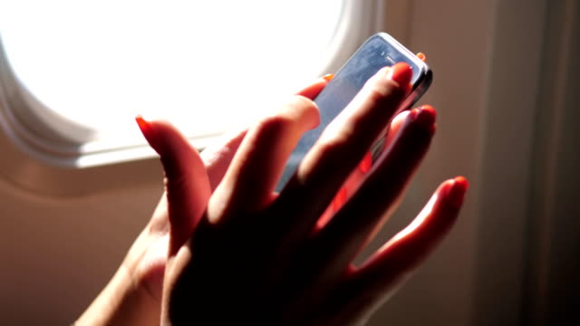 Closeup Of Woman's Hand Using The Telephone, Sitting At The Window Of The Plane video