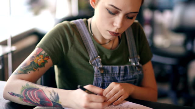 Closeup of young attractive red haired woman tattoo artist sitting at table and creating sketch for tattooing in studio indoors video