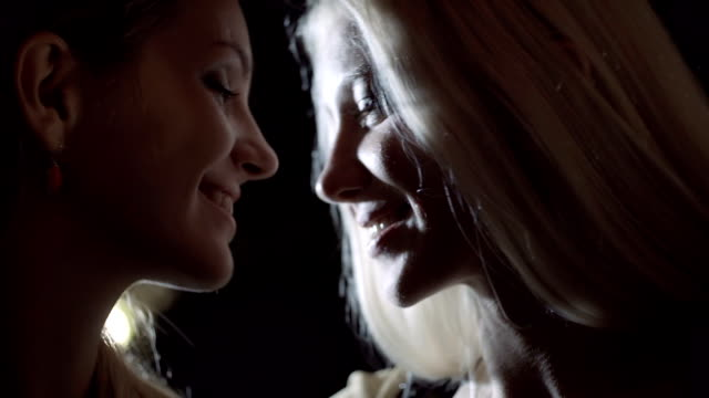 Close-up of young beautiful homosexual lesbian woman couple, with teasing, smile at night - slow-motion HD video footage video