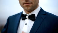 A close-up outdoor shot of elegant man wearing a tux and bow-tie video