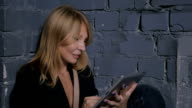 Close-up - pensive woman using a tablet and sits near the stone wall video
