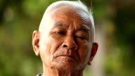close-up portrait of a asian senior man thinking about something video