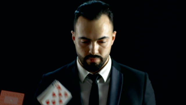 Close-up Portrait of a Bearded Magician Looking at the Camera and Gaming Cards Raining on Him then He Pulls Ace of the Deck. video