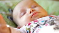 close-up portrait of a beautiful sleeping baby in bed video