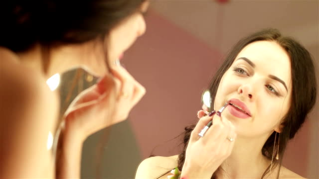 closeup portrait of beautiful young lady applying pink lipstick in front of mirror, nude make up video