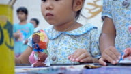 Closeup portrait of little girl learning painting with child hand to white plaster doll toy video