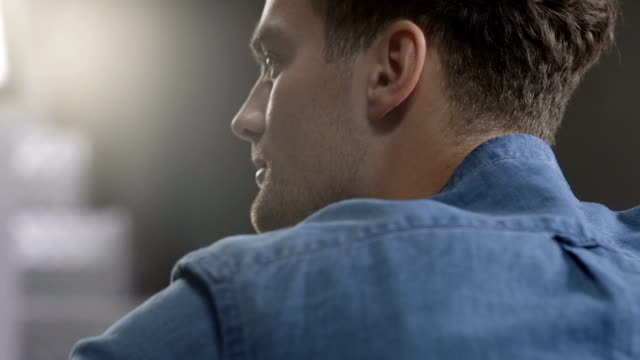 Closeup portrait of young handsome man in blue shirt looking to a camera. video