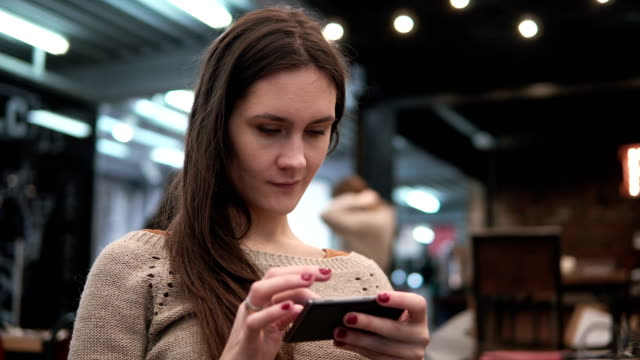 Closeup portrait. Woman using her smartphon touchscreen device in modern cafe 4k video