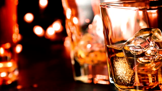 close-up pouring whiskey in the glass on bar table near bottles video