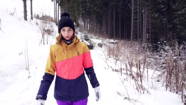 Closeup profile of young woman walking in winter forest during the snow falling video