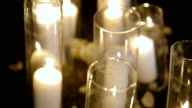 Closeup Romantic burning white candles in glass vases standing on a grass for an evening wedding ceremony. video