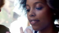 Close-up sexy black women sitting in a cafe with her friends. She bites her lip video