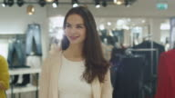 Close-up shot of a happy young brunette girl that is walking though a clothing store. video