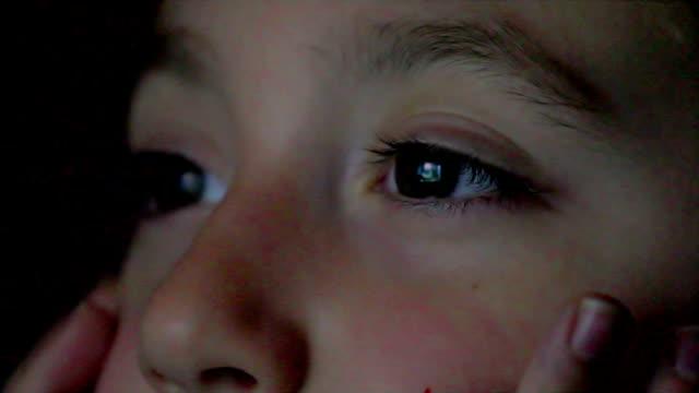 Closeup shot of boy eyes watching television at night video